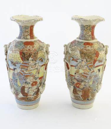 A pair of Japanese Satsuma vases, decorated with figures in a lavish interior,