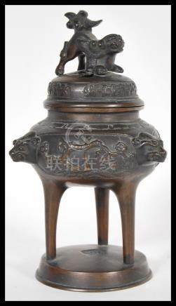 A 19th Century Chinese bronze censer ding incense burner raised on circular base with Foo dog mask