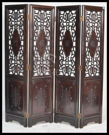 A large 20th Century Chinese padauk wood four panel folding discretionary screen room divider having