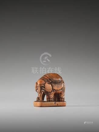 A WOOD NETSUKE OF A CAPARISONED ELEPHANT ON A BASE