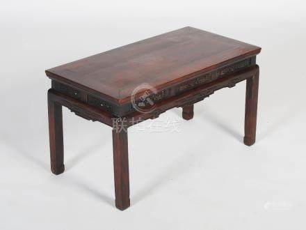 A Chinese dark wood low table, Qing Dynasty, the rectangular panelled top above a pierced and scroll