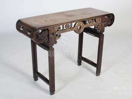 A Chinese dark wood table, Qing Dynasty, the rectangular panelled top above a frieze centred with