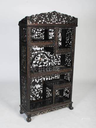A Chinese dark wood display cabinet, Qing Dynasty, the upper section carved with a pair of dragons