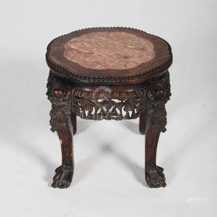 A Chinese dark wood jardiniere stand, Qing Dynasty, the shaped circular top with a mottled red