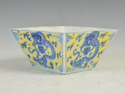 A Chinese porcelain yellow ground blue and white tapered square dragon bowl, Qing Dynasty, the