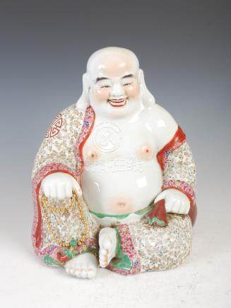 A Chinese porcelain figure of a laughing Buddha, late 19th/ early 20th century, decorated in