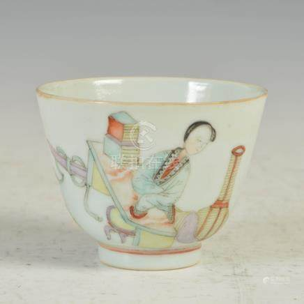 A Chinese porcelain tea bowl, Qing Dynasty, decorated with a female kneeling before a table, iron