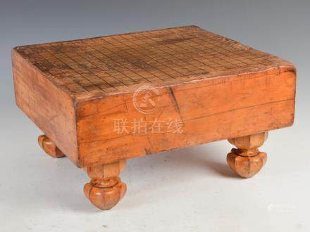 A Chinese table top blonde wood Go board, Qing Dynasty, with black lacquer divisions, raised on four