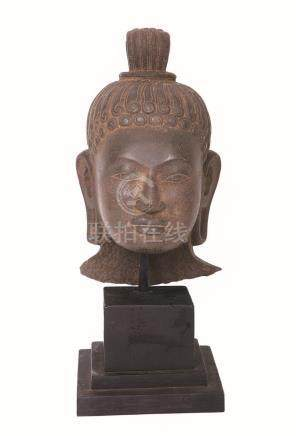 A CARVED STONE HEAD OF BUDDHA