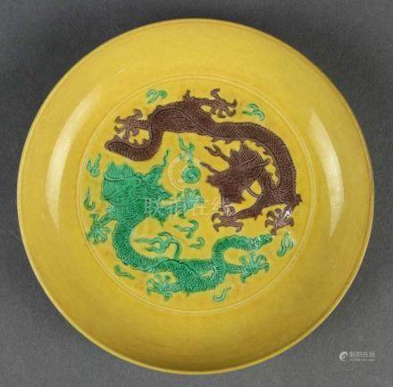 Chinese enameled porcelain dish, featuring one aubergine and one green dragon chasing a jewel on