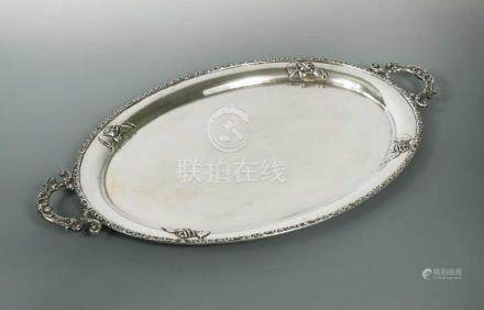 A German metalwares oval tray, by Handarbeit, with floral border and two applied scrolling