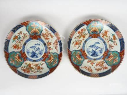 Paire de plats en porcelaine d'Imari à décor en médaillon d'une scène paysagée,