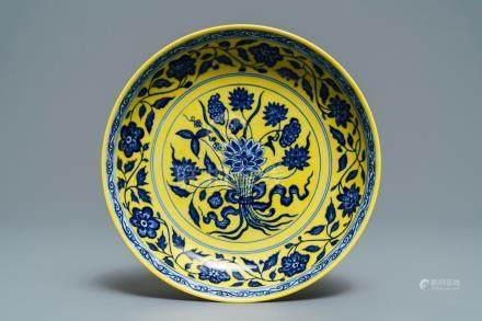 A Chinese yellow-ground blue and white 'lotus bouquet' plate, Qianlong mark, 19/20th C.
