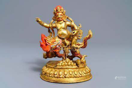 A Sino-Tibetan painted gilt bronze figure of Jambhala on a dragon, 19/20th C.