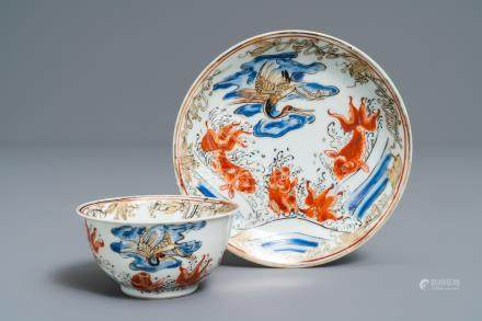 A Chinese iron red, grisaille, gilt and overglaze blue 'carps and crane' cup and saucer, Yongzheng