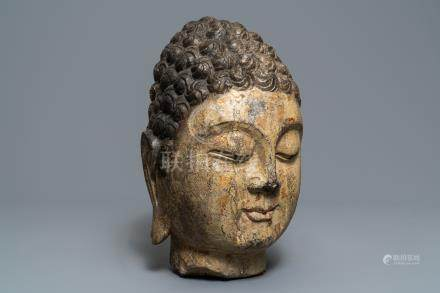 A Chinese carved stone head of Buddha with traces of gilding and polychromy, Ming