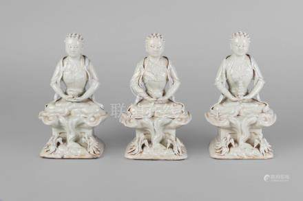 Three Chinese porcelain seated figures of Lohan, 19th century, with pale crackle glaze, each