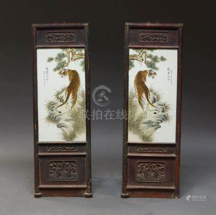 A pair of Chinese porcelain plaques decorated with tigers, late 20th century, within rock and pine