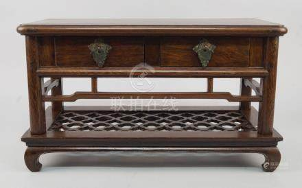 A Chinese hongmu table top stand, 19th century, with two drawers and openwork frieze, on a kang