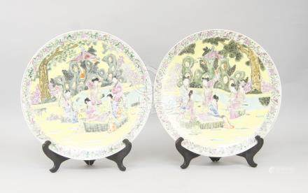 A pair of Chinese porcelain plates, late 20th century, decorated with ladies playing go in formal