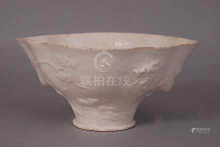 C18th Chinese Dehua libation cup, moulded with dragon, tiger, deer, crane and flowering branches,