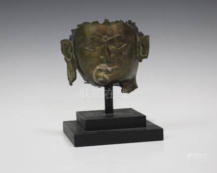 A Chinese bronze Buddha head fragment, probably 17th century, mounted on an ebonized stand, total