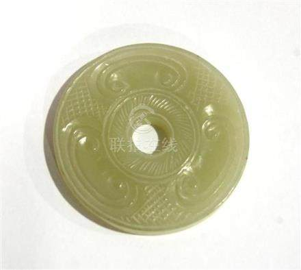 A Chinese Celadon Jade Bi Disc, Carved with C Scrolls,