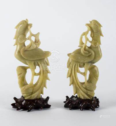 A pair of Chinese bowenite carved stone birds on wooden stan