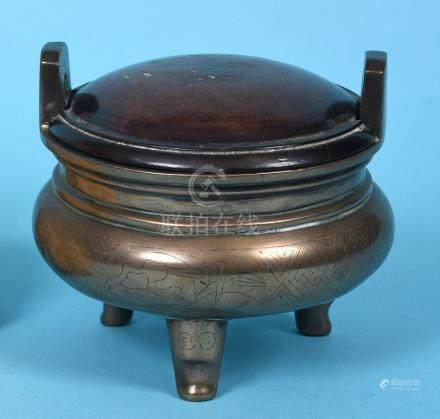 A Chinese bronze censer, of compressed circular form, with an associated wood cover and three