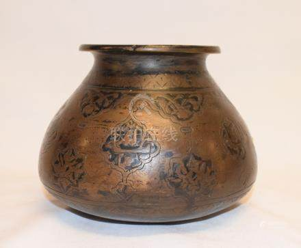 An Islamic brass vessel, of compressed baluster form, decorated foliage and calligraphy, 12 cm high