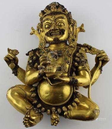 An early 20th century Sino-Tibetan gilt bronze of a seated Mahakala,the wrathful Diety having a