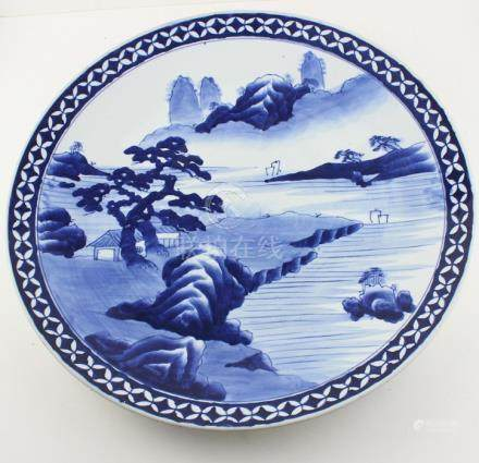 A 19th century oriental Kangxi style large blue and white charger decorated centrally with a