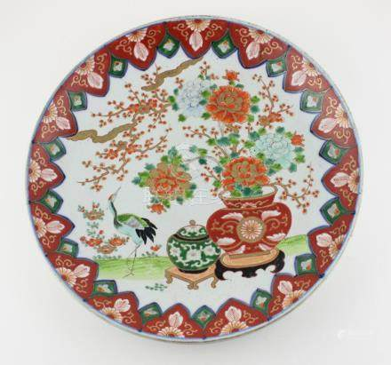 A Japanese Meiji period porcelain charger, decorated with blossom and Crane, diameter 37.1cm.