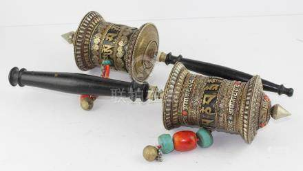 Two Tibetan brass and silvered prayer wheels, with inscription bands and jewelled glass bead