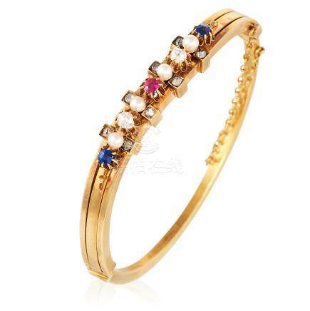 AN ANTIQUE RUBY, SAPPHIRE, PEARL AND DIAMOND BANGLE in high carat yellow gold, the undulating body