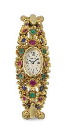 Cartier. A fine, rare and very attractive 18K gold, emerald, ruby and sapphire-set lady's backwound bracelet watch with integral bracelet