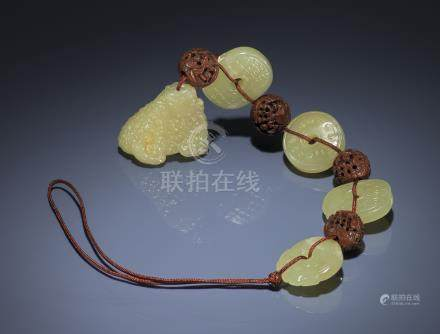A STRING OF YELLOW JADE AND CARVED FRUIT KERNEL BEADS, DUOBAOCHUAN