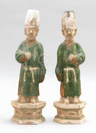 PAIR OF POTTERY FIGURES In the form of attendants on hexagon