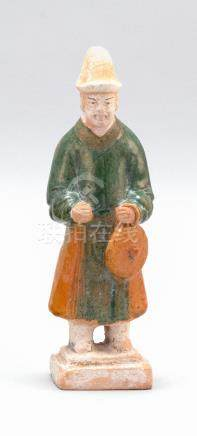 CHINESE POTTERY FIGURE Depicting a standing attendant holdin