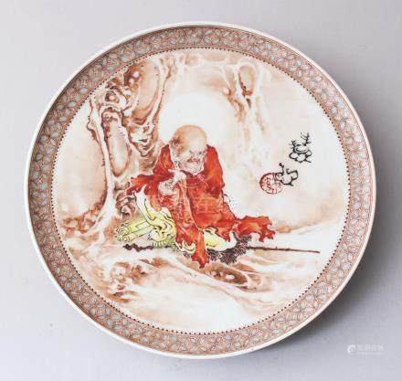 A CHINESE REPUBLICAN STYLE ENAMELLED PORCELAIN DISH, depicting scenes of a luohan resting under a