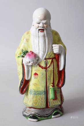 A GOOD CHINESE PORCELAIN MODEL OF GOD SHOU LOU, stood holding a fruit of some kind, wearing
