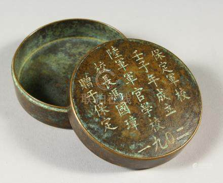 A SMALL CHINESE CIRCULAR BRONZE BOX AND COVER, with calligraphy inscription. 7.5cms diameter.