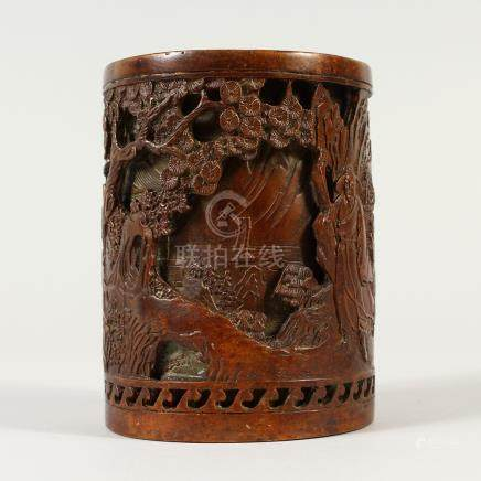 A CHINESE BRONZE BRUSHPOT, decorated with figures in a landscape. 14cms high.