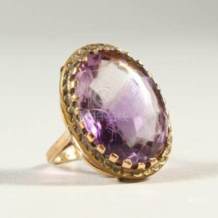 A GOLD RING SET WITH A LARGE AMETHYST COLOURED STONE.