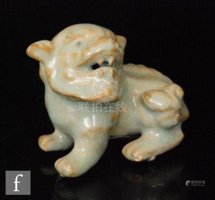 A Chinese celadon glazed figure of a Shishi, modelled in seated position,