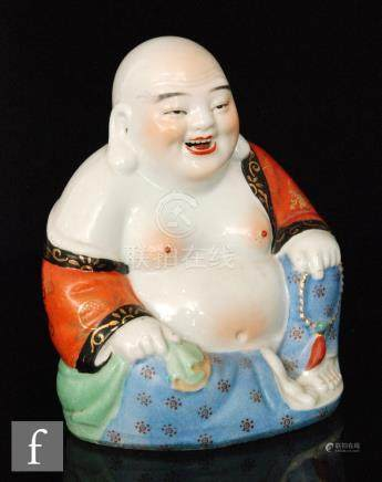 A Chinese Republic style figure of a laughing Buddha, the white glazed figure in seated position,