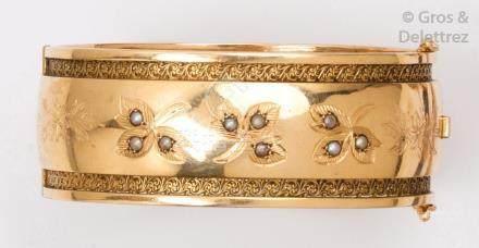 Bracelet jonc ouvrant en or jaune ajouré et ciselé, à décor de feuillage sertis