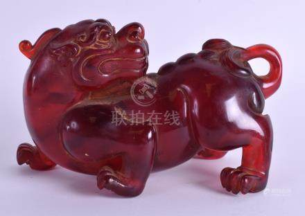 A CHINESE CARVED DOG OF FOE possibly red amber. 17 cm wide.