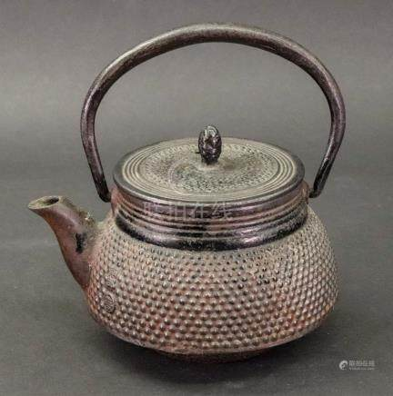 A small Japanese iron tetsubin, 19th century, of compressed form with overhead swing handle, signed,