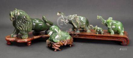 A group of Chinese green hardstone figures, 20th century, comprising:- a family of three elephants,